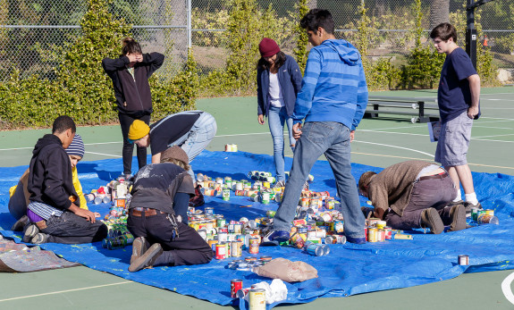 Garden Street Academy Students Assembling Canned Food Mosaic Art Piece